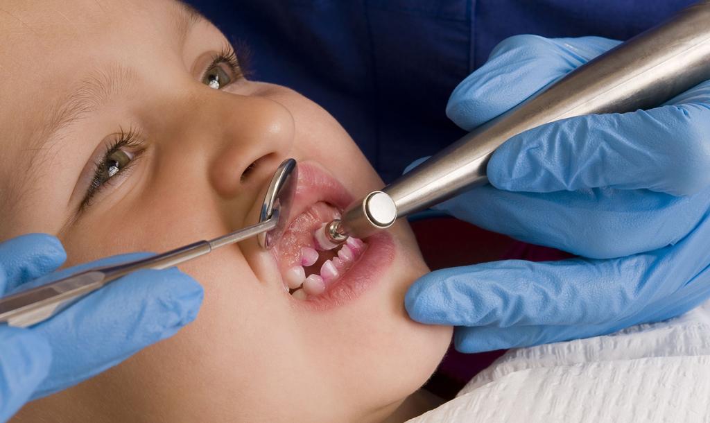 На фото показана профессиональная чистка зубов ребенку